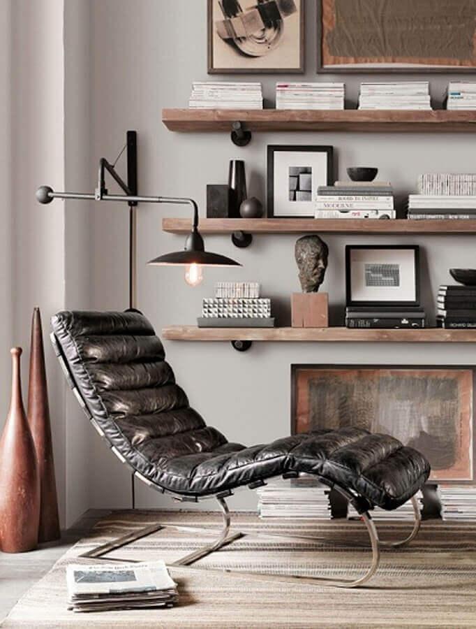 Poltrona preta de couro para decoração de sala com prateleiras de madeira