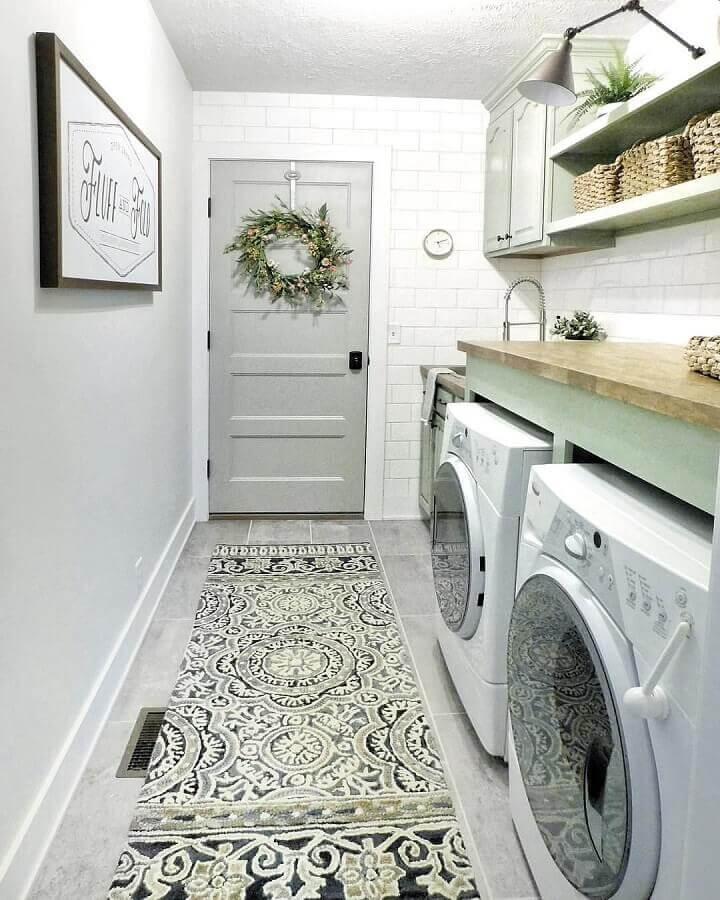 Prateleira para lavanderia decorada em tons de cinza com bancada de madeira