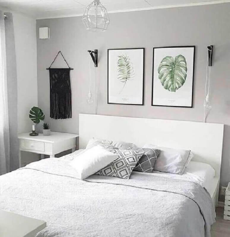 Quarto cinza claro decorado com cabeceira branca e quadro de folhagem