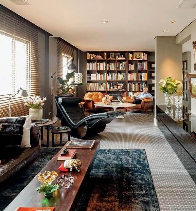 Sala ampla decorada com sofá de couro e poltrona preta moderna