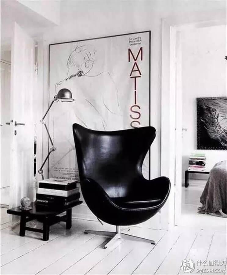 Sala branca com estilo minimalista decorada com poltrona giratória preta