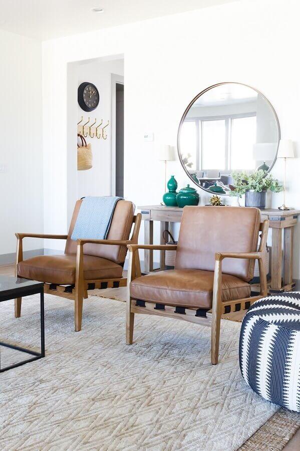 sala clean decorada com espelho redondo e poltrona marrom de madeira Foto Style me Pretty