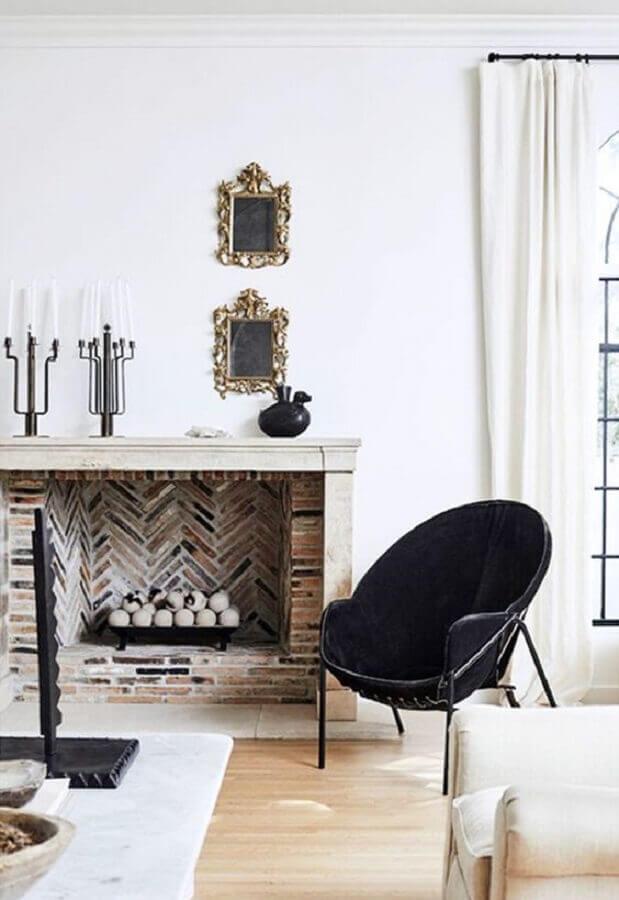 Sala com lareira decorada com poltrona preta redonda