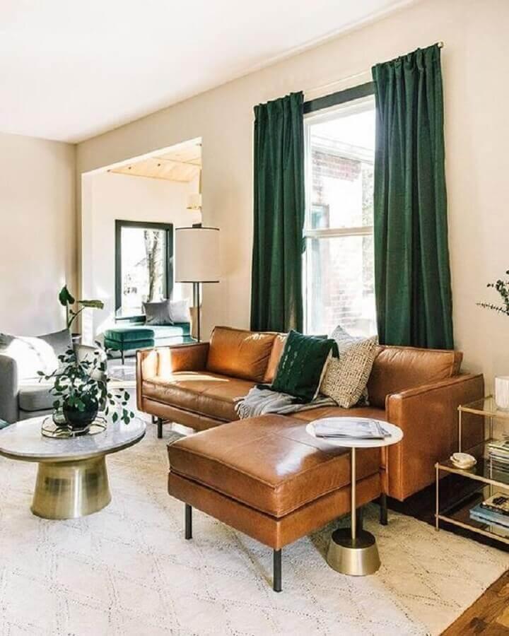 Sala de estar decorada com sofá de couro com chaise e cortina na cor verde escuro