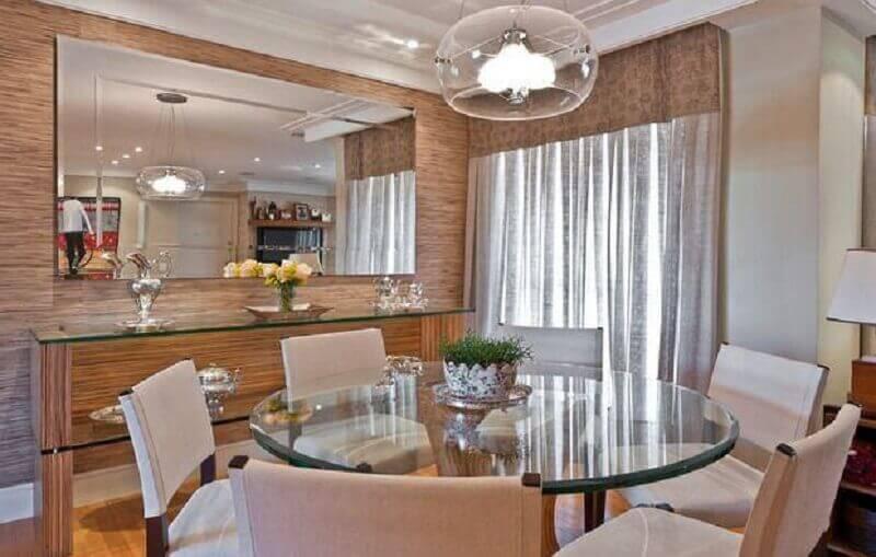 Sala de jantar com espelho e aparador decorada com mesa redonda de vidro