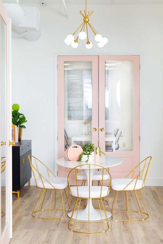 Sala de jantar com lustre branco e detalhes em dourado