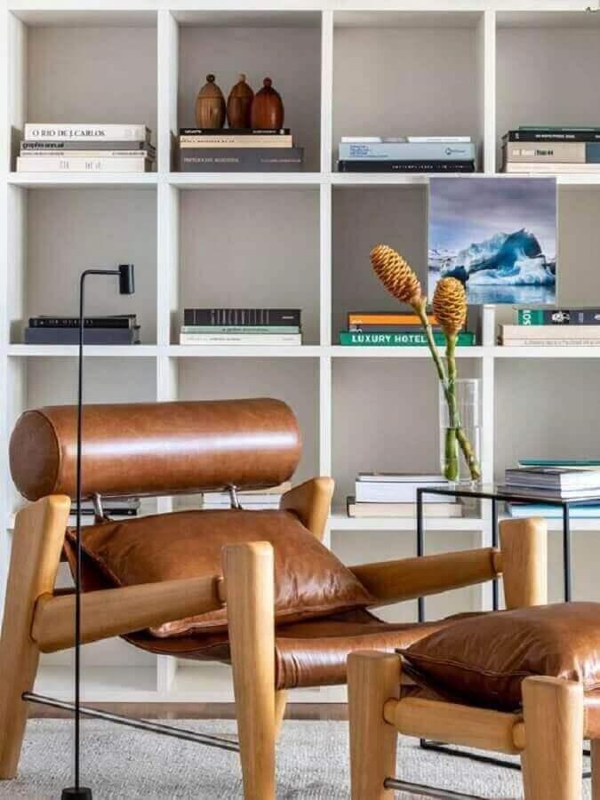 sala decorada com estante de nichos e poltrona marrom moderna de couro  Foto Casa de Valentina