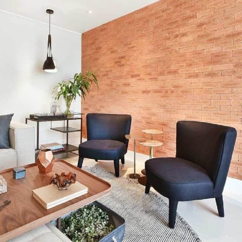 Sala decorada com parede tijolinho e poltrona preta sem braço