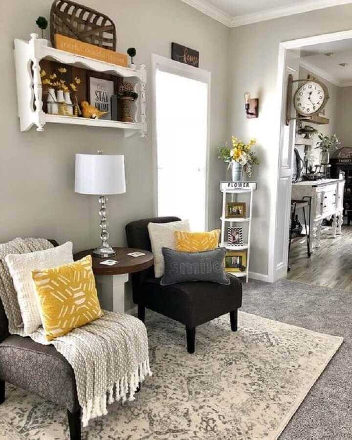 Sala em tons de cinza decorada com poltrona preta sem braço