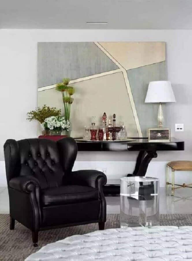 Sala sofisticada decorada com poltrona preta capitonê antiga