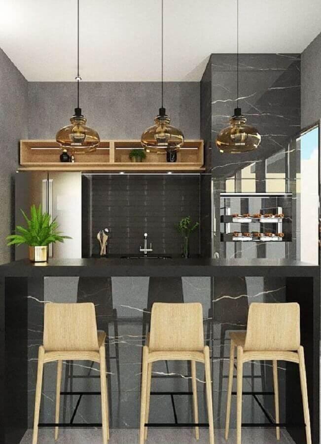 área gourmet moderna com churrasqueira decorada com mármore preto e luminária de vidro Foto Archtrends