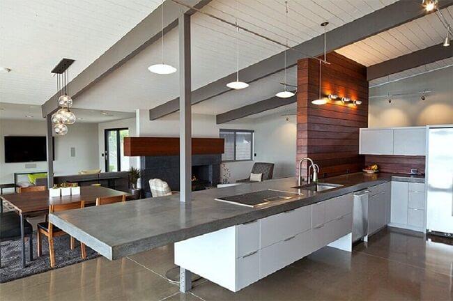 A bancada de cimento queimado extensa se destaca na decoração da cozinha. Fonte: Limaoagua