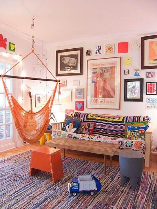 A cadeira de rede laranja se mistura na decoração da sala de estar