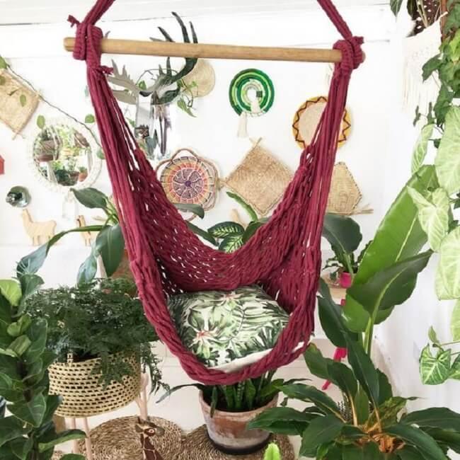 A cadeira rede de teto vinho se destaca em meio as folhagens