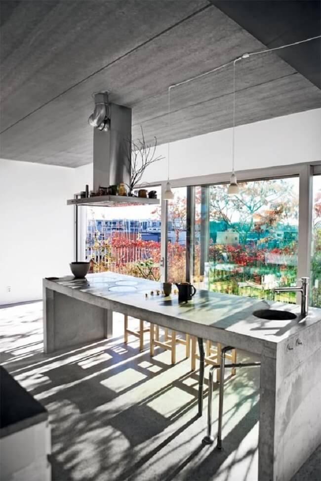 A iluminação natural invade a cozinha e realça a presença da bancada de cimento queimado. Fonte: Pinterest
