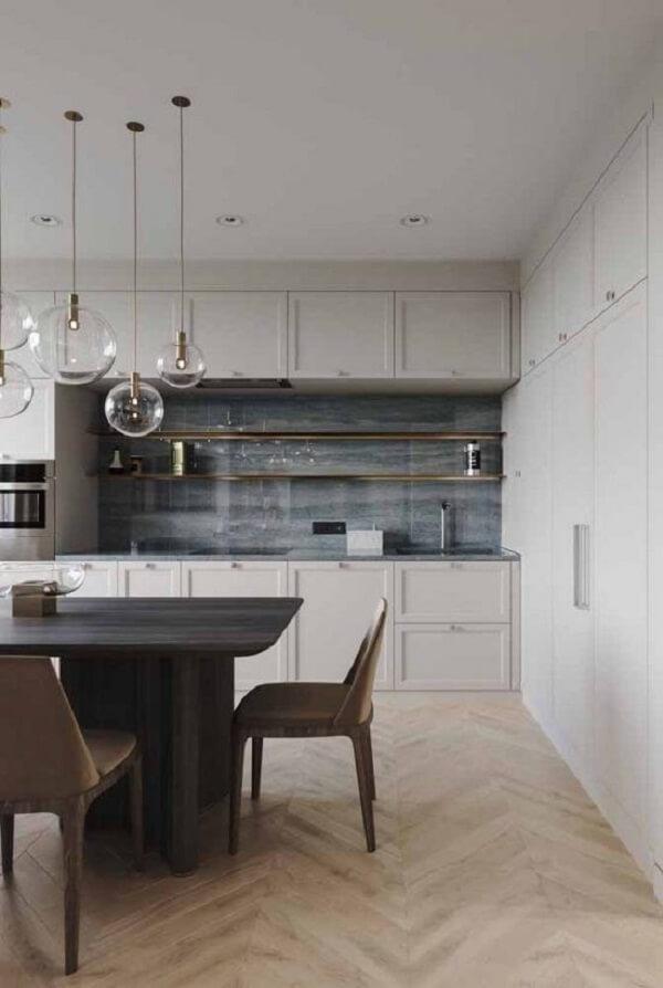 A marcenaria branca da cozinha conta com uma linda bancada feita em silestone cinza claro