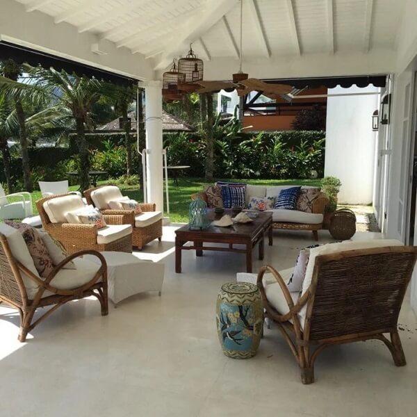 A mesa de centro em madeira se conecta com o jogo de sofá de vime