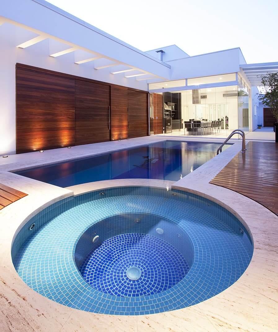 A piscina infantil redonda se interliga com a piscina maior em formato retangular. Fonte: Homepedia