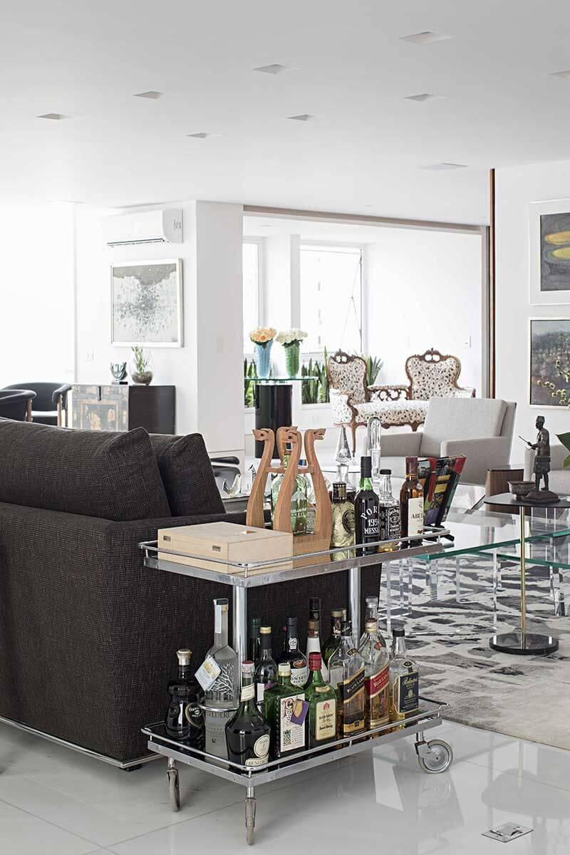 Aparador bar ao lado do sofá preto na sala chique