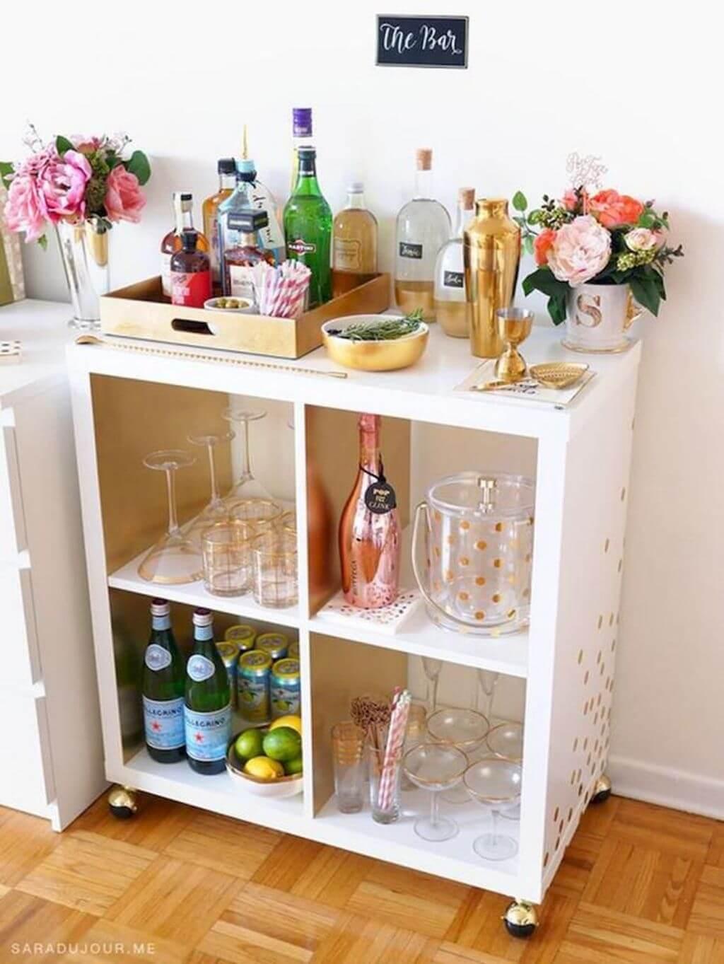 Aparador bar branca com bandeja dourada e taças de vidro