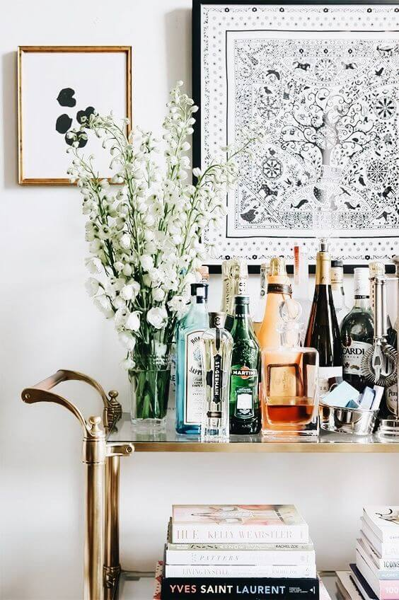 Aparador bar com vaso de flores e bebidas