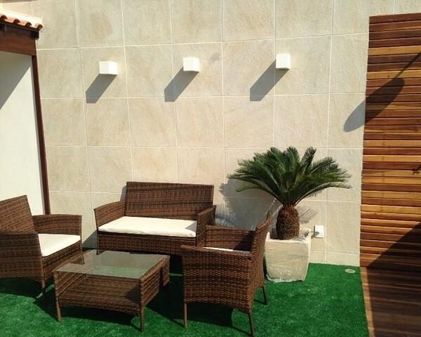 Arandelas metálicas e piso com grama artificial