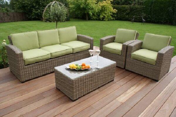 As almofadas em tom verde do sofá de vime se misturam com a grama do jardim