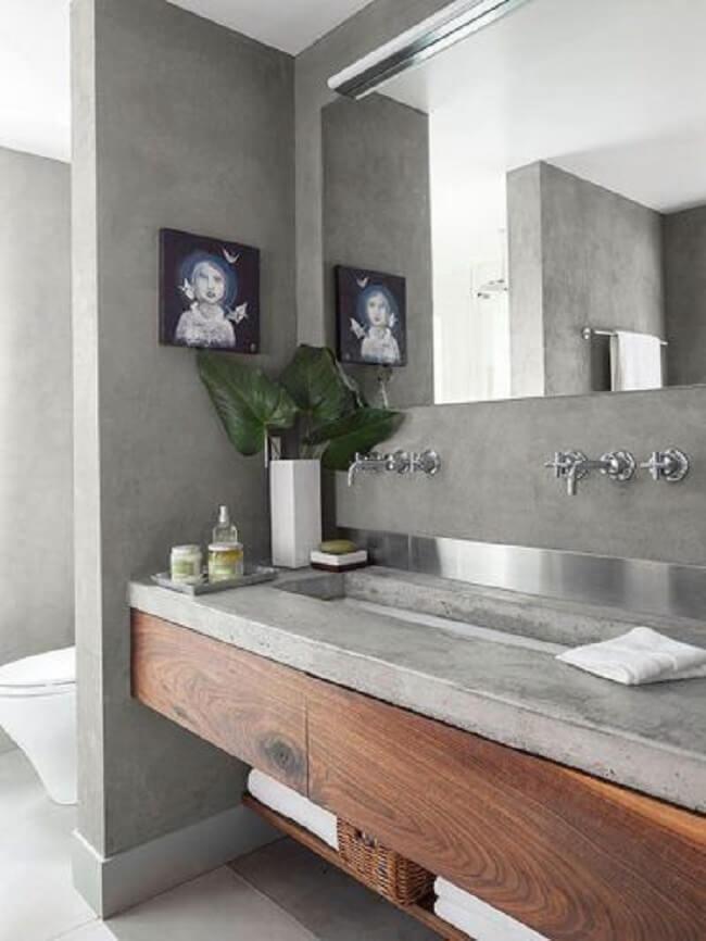 Bancada de cimento queimado banheiro com elementos em madeira. Fonte: Conexão Décor