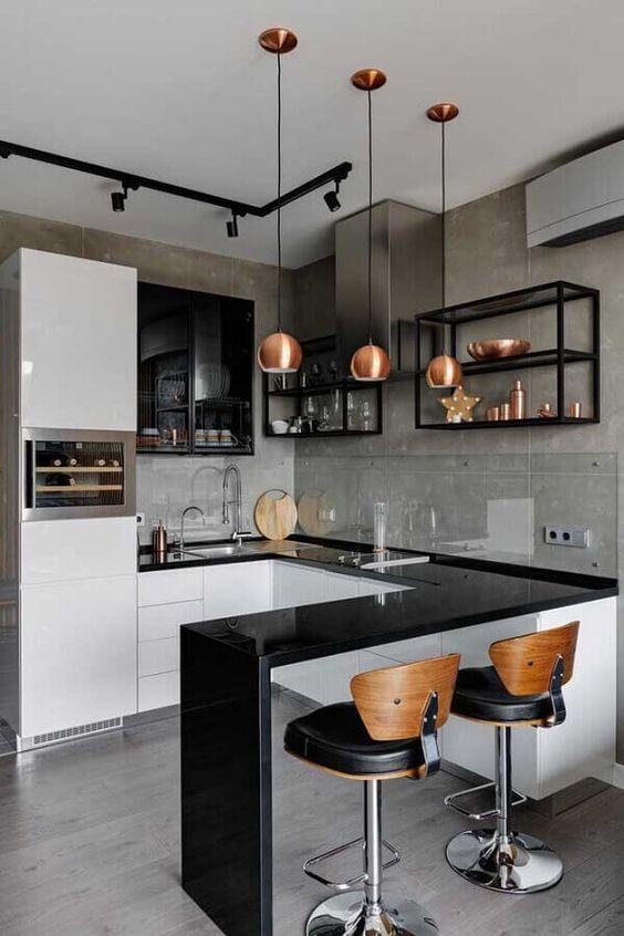 Bancada de granito preto em U na cozinha com armários brancos e prateleiras de ferro industrial