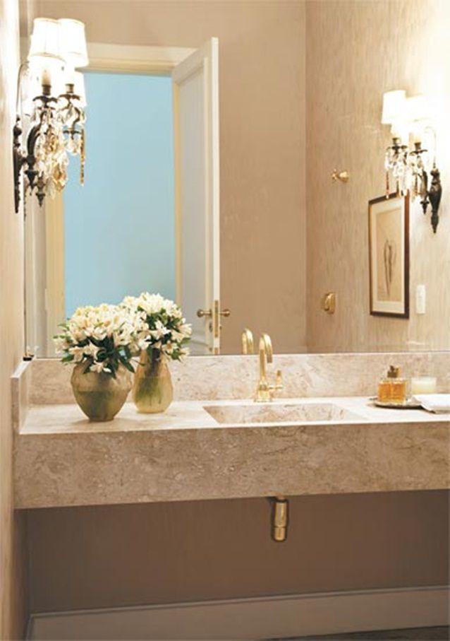 Banheiro com bancada de granito e torneira dourada