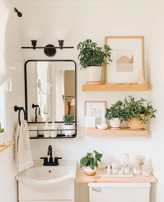 Banheiro com prateleira rustica e decoração com quadros e plantas