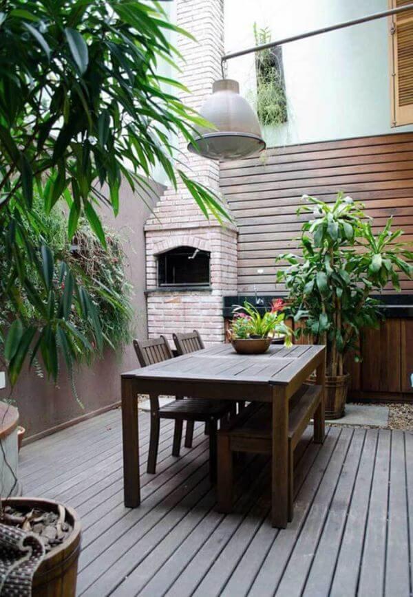Quintal com churrasqueira de tijolinho na decoração charmosa
