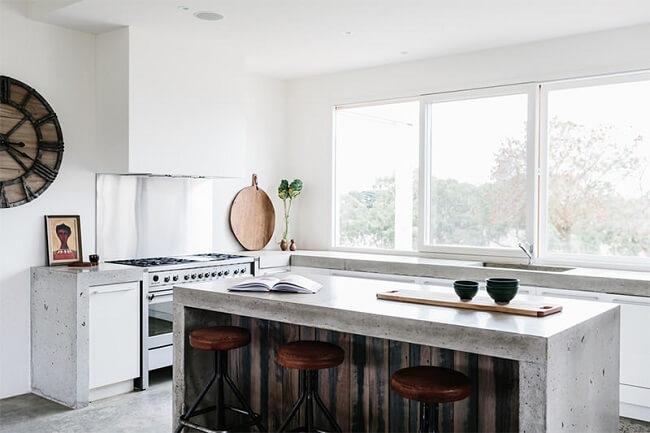 Cozinha bem iluminada com bancada de cimento queimado. Fonte: Greig Design & Construction