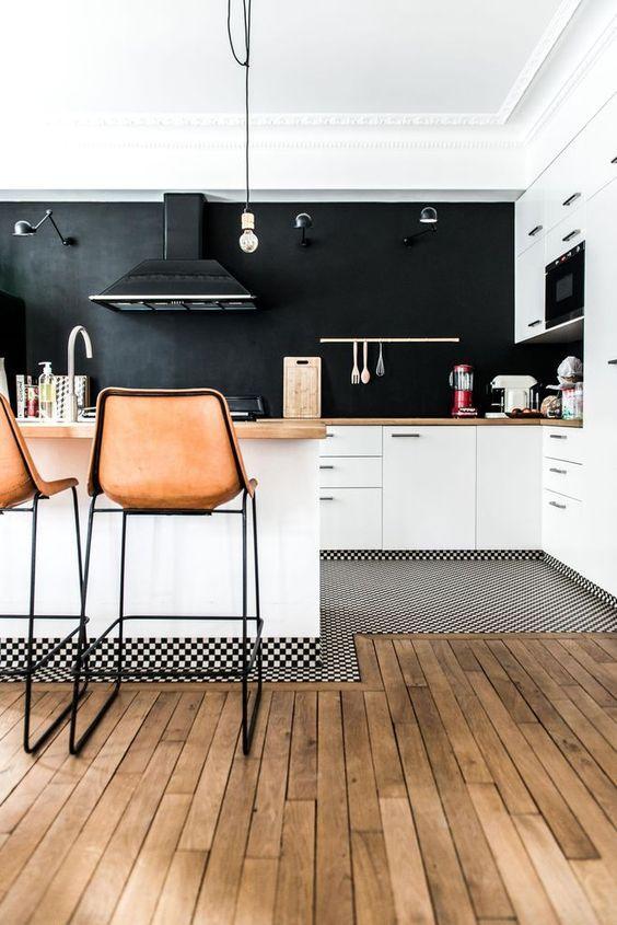 Cozinha com armários brancos e tinta lousa preta