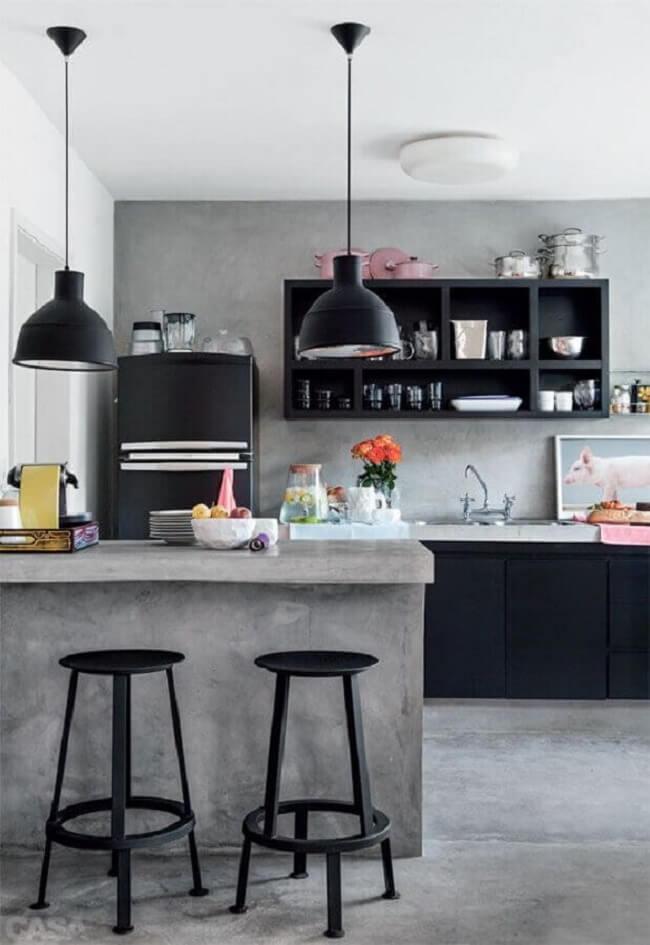 Cozinha com bancada de cimento queimado e armários pretos planejados. Fonte: Futurist Architecture