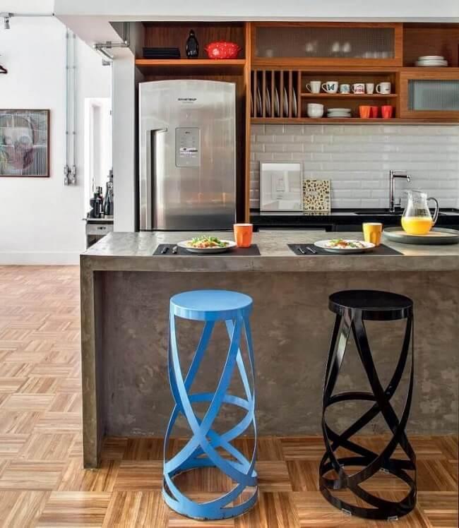 Cozinha com bancada de cimento queimado e banquetas modernas. Fonte: Decostore