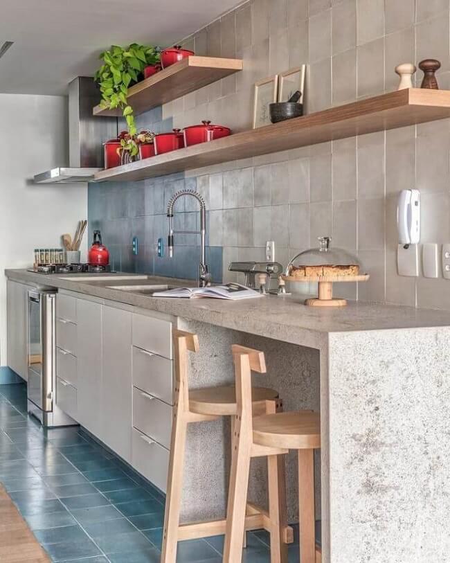 Cozinha com prateleiras de madeira e bancada de cozinha de cimento queimado. Fonte: Voa Arquitetura