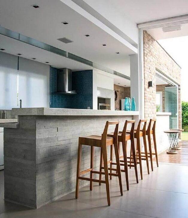 Cozinha gourmet com bancada de cimento queimado e banquetas de madeira. Fonte: Gauss Revestimentos