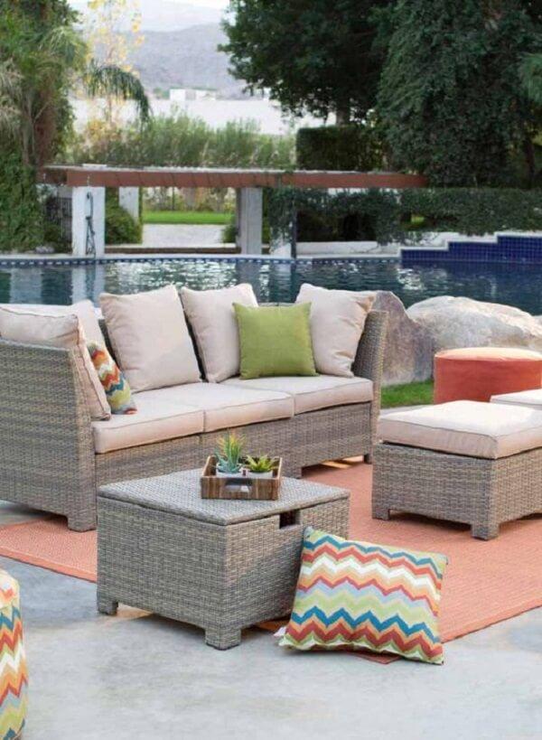 Crie um espaço confortável com sofá de vime próximo a área da piscina