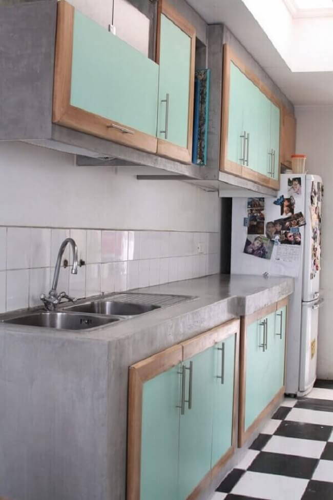 Decoração simples com bancada de cozinha de cimento queimado e armários com portas verdes. Fonte: Arquidicas