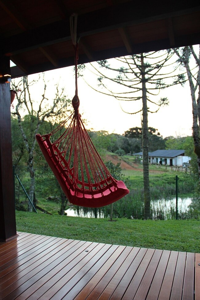 Decore a varanda da casa de campo com uma linda rede cadeira suspensa