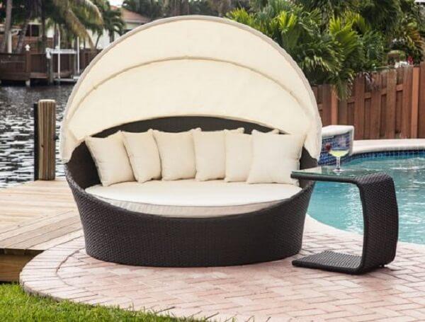 Esse modelo de sofá de vime redondo fica perfeito na área da piscina