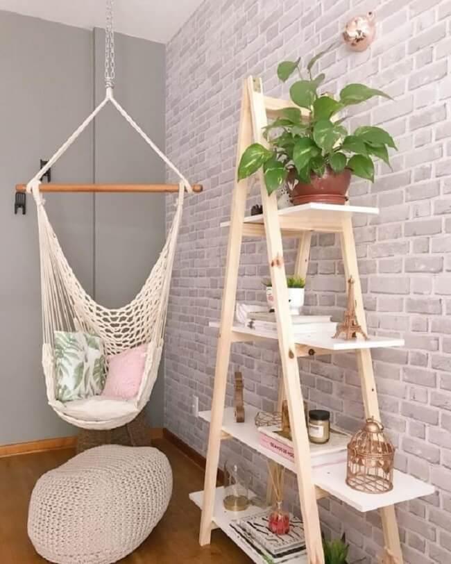 Estante escada e rede cadeira suspensa decoram o ambiente
