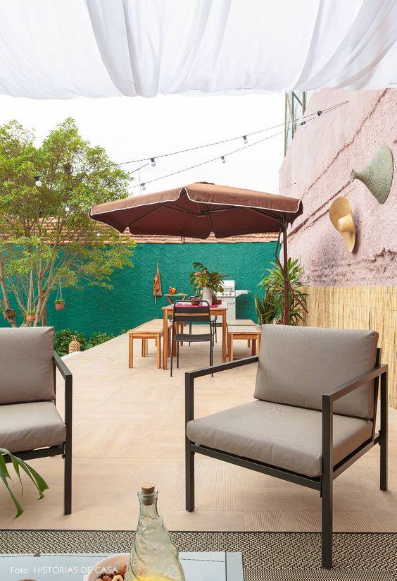 Mesa de jardim com guarda sol e poltronas cinza