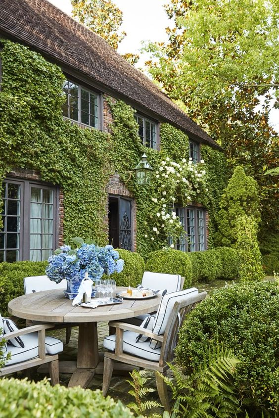 Mesa de jardim de madeira redonda e vaso de flores
