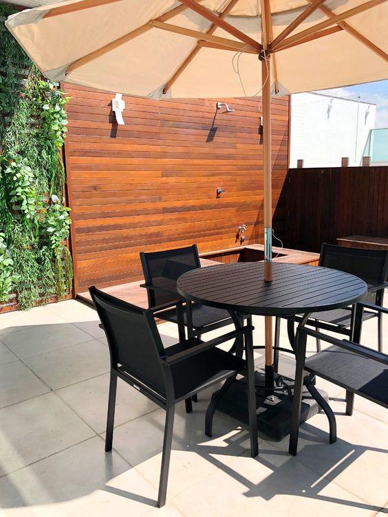 Mesa de jardim preta com ombrelone
