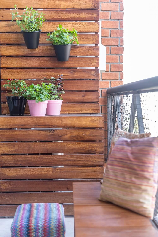 O banco de madeira traz leveza, conforto e as ripas da parede serve de suporte para vasos de plantas. Foto: JP Image