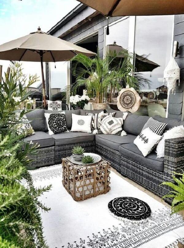 O ombrelone minimiza a presença do sol sobre aqueles que sentam no sofá de vime