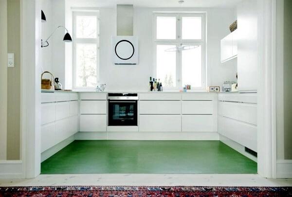 O piso colorido em cimento queimado na cor verde quebra a neutralidade da cozinha