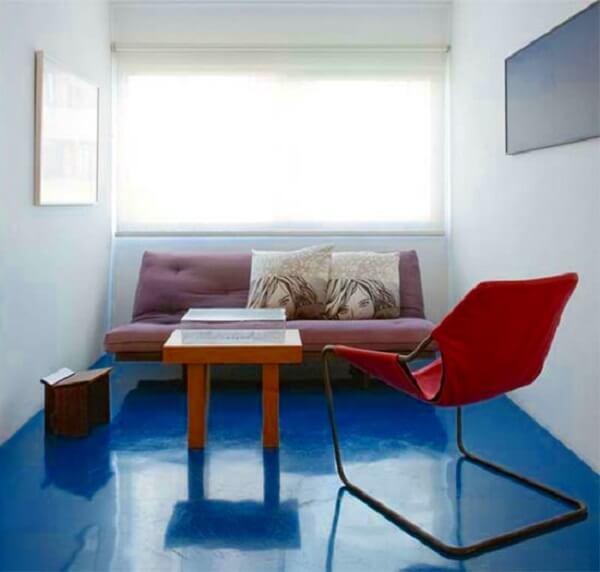 O piso queimado colorido em tom azul é o grande destaque dessa sala de estar